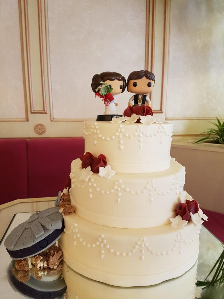 Hochzeitstorte mit Blumen und Hochzeitspaarfiguren