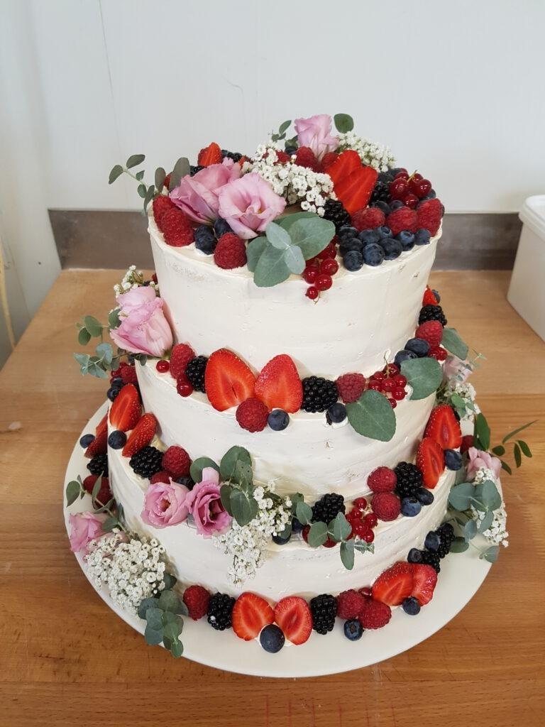 Hochzeitstorte mit Waldfrüchten und Blumen