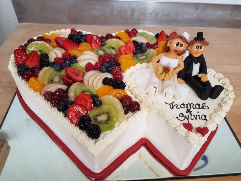 Hochzeitstorte in Doppelherzform mit Obst und Ehepaarfiguren