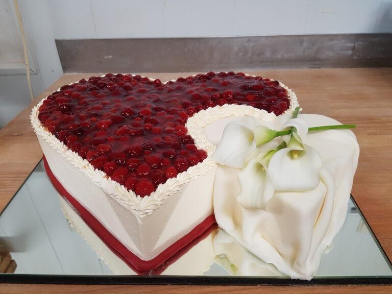 Hochzeitstorte in Doppelherzform mit Früchten und Blume
