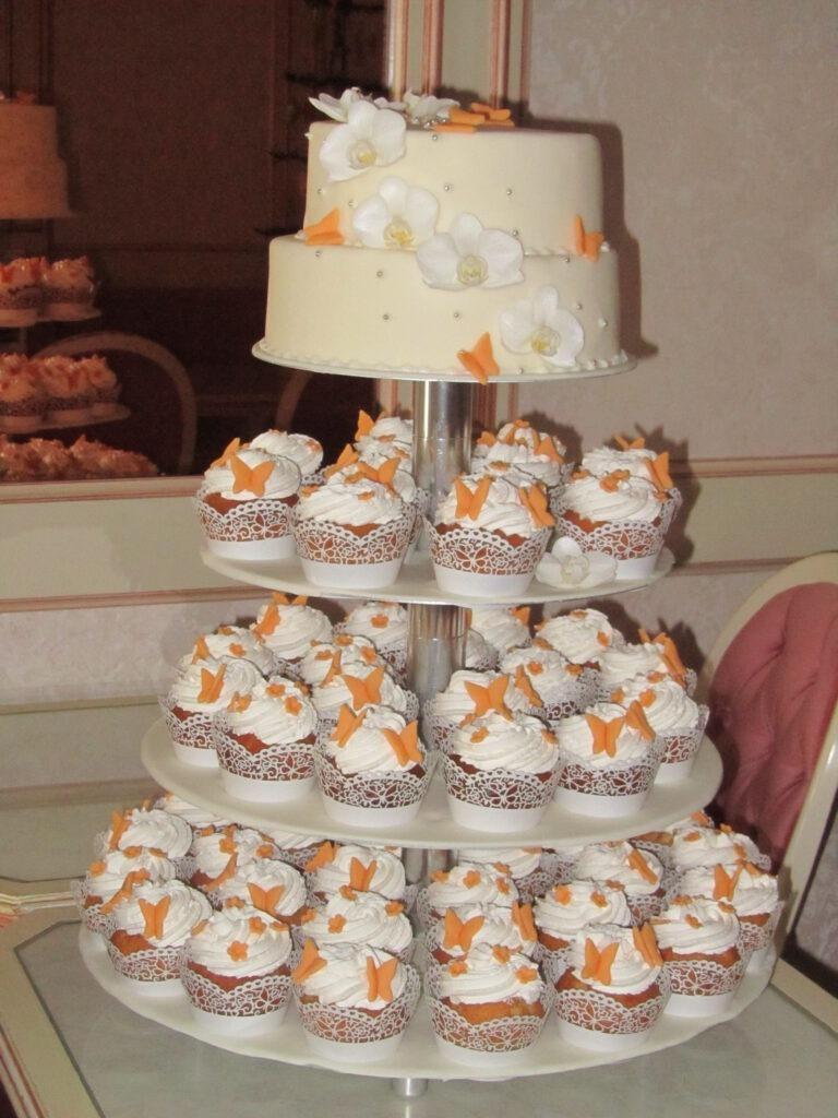 Hochzeitstorte mit extra Muffins und orangenen Schmetterlingen