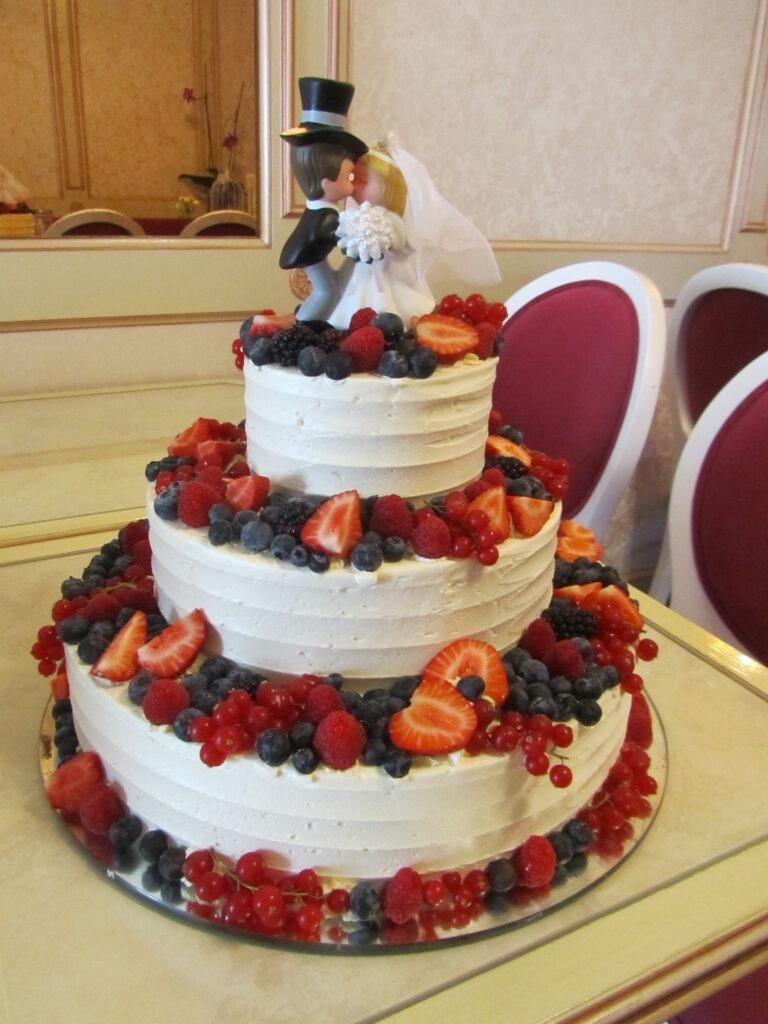 Hochzeitstorte mit Waldfrüchten und Brautpaar
